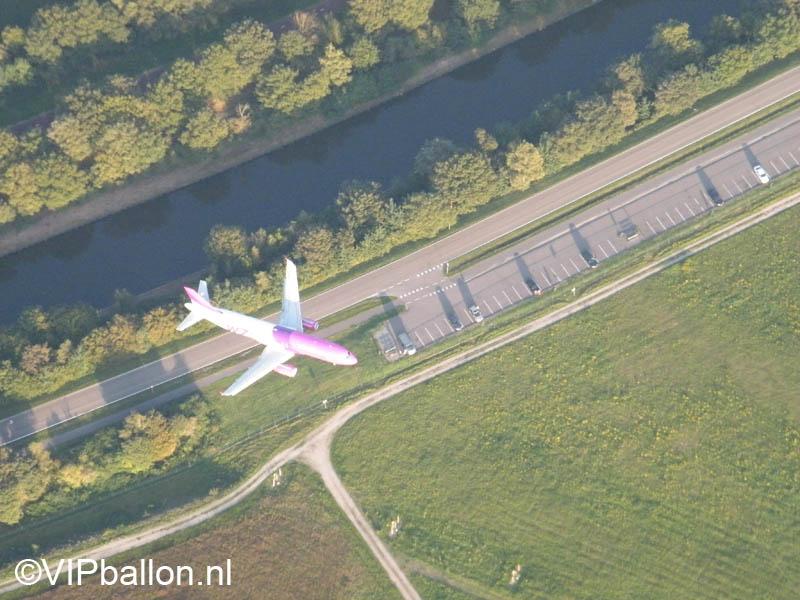 Een Wizzair vliegtuig land onder ons op Eindhoven Airport.